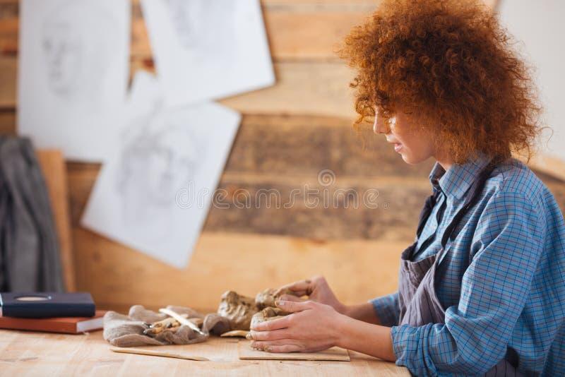 Fokuserad kvinnaceramist som skapar skulptur genom att använda lera i krukmakeriseminarium arkivbilder