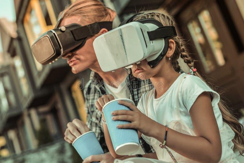 Fokuserad långhårig dotter som äter popcorn, medan hålla ögonen på film arkivbild