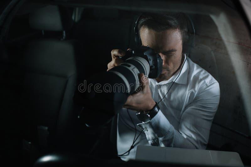 fokuserad manlig privat kriminalare i hörlurar som gör bevakning vid kameran arkivbilder