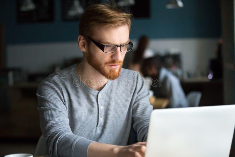 Fokuserad millennial man som använder bärbar datorarbete i kafé royaltyfri bild