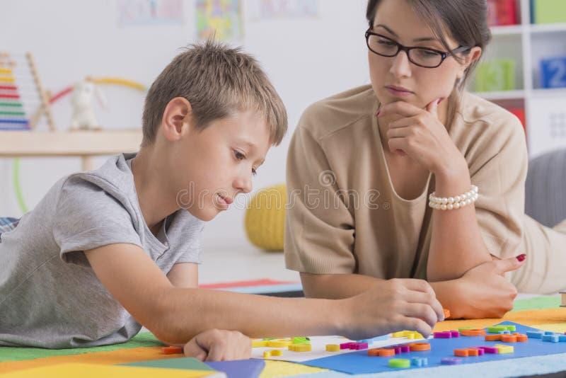 Fokuserad pojke och nätt psykoterapeut royaltyfria bilder