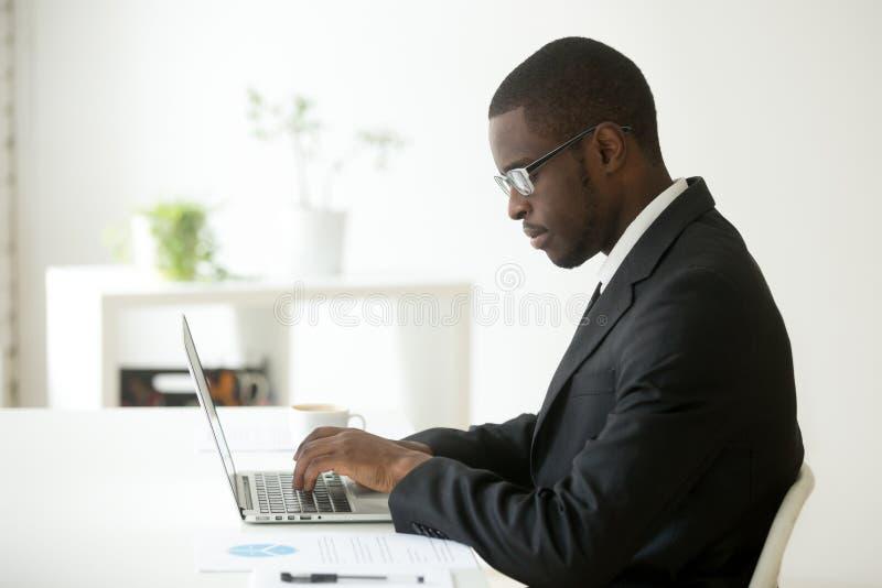 Fokuserad svart arbetare som arbetar på bärbara datorn på företagsarbetsplatsen royaltyfria foton