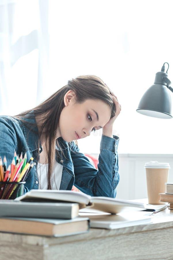 fokuserad tonårs- flicka som tar anmärkningar och att studera arkivbild