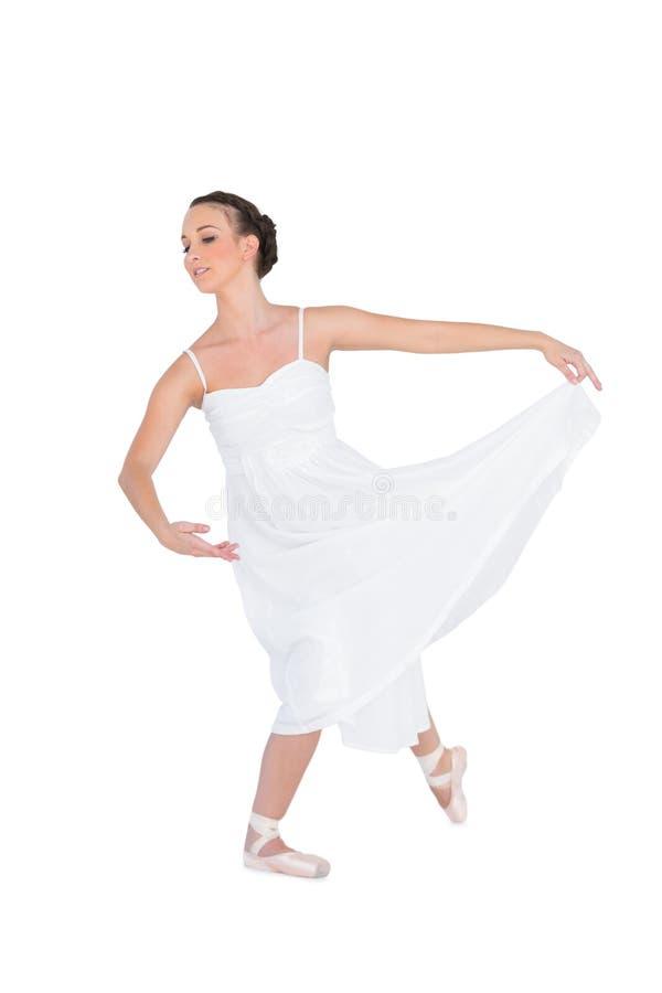 Fokuserad ung balettdansör som poserar med hennes ben tillbaka royaltyfri fotografi