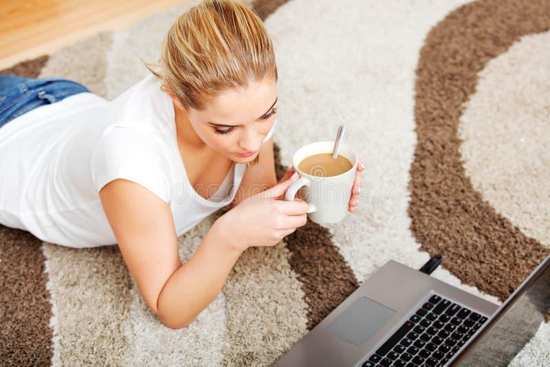Fokuserad ung kvinna som använder bärbara datorn, medan ligga på golv och dricka kaffe arkivfoton