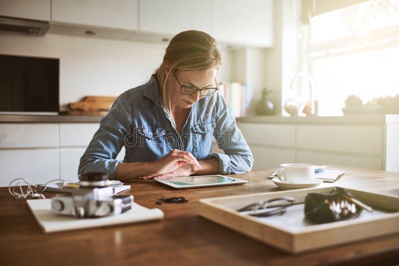 Fokuserad ung kvinnlig entreprenör som arbetar på hennes affär på hom arkivbild