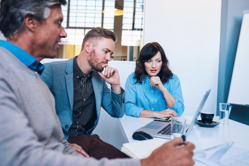 Fokuserade businesspeople som tillsammans arbetar på en bärbar dator i ett kontor arkivfoton