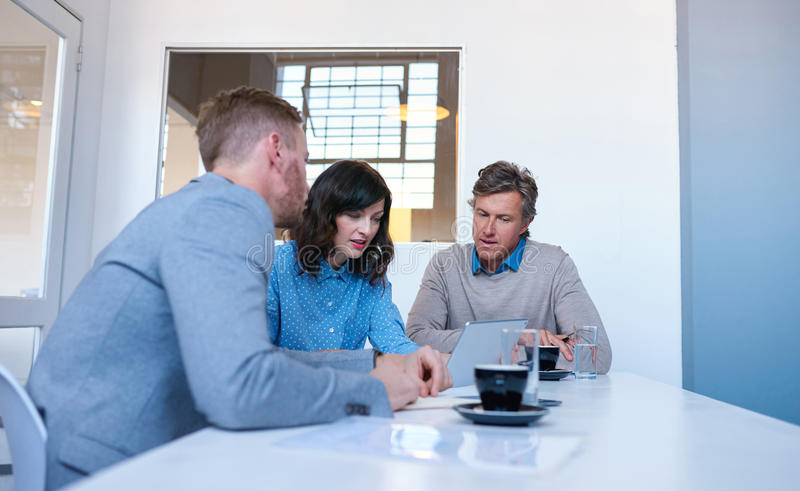Fokuserade coworkers som tillsammans använder en digital minnestavla i ett kontor arkivfoto