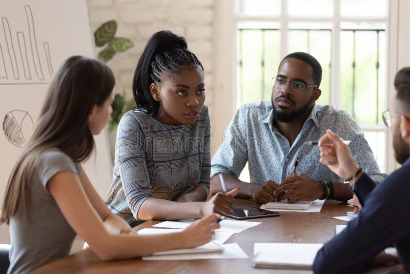 Fokuserade kvinnliga anställda inom den svarta chefsundervisningen i samband med genomgång av kontor royaltyfri foto