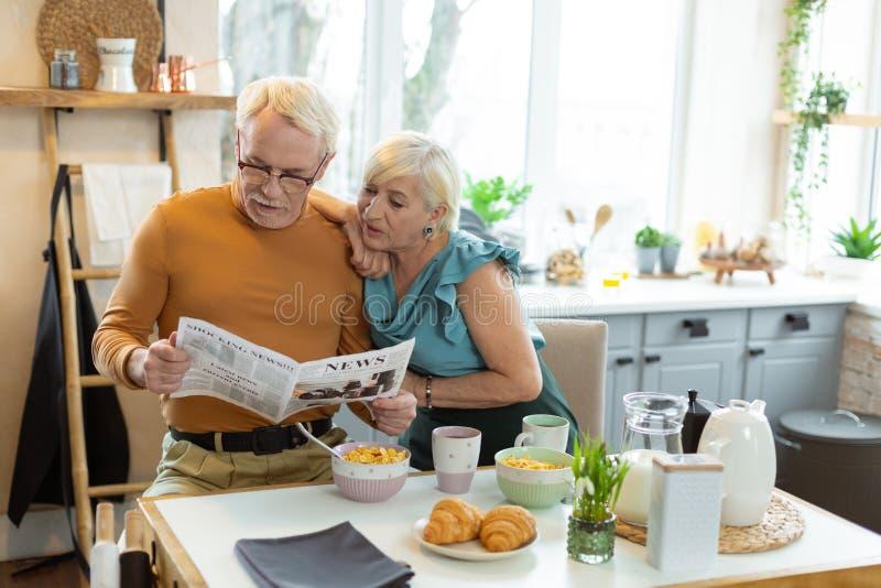 Fokuserade maker som läser tidningen, medan sitta på köksbordet arkivfoto