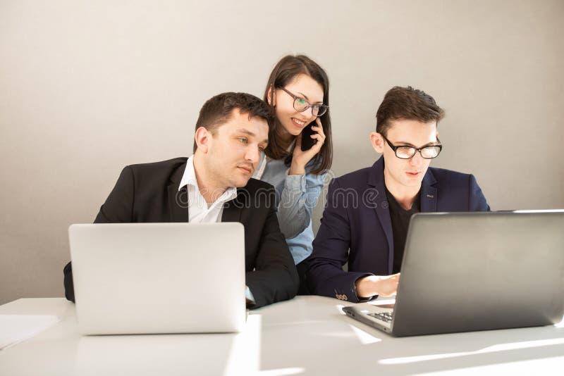 Fokuserat affärsteam som arbetar, kvinna som pratar på mobiltelefon arkivbilder