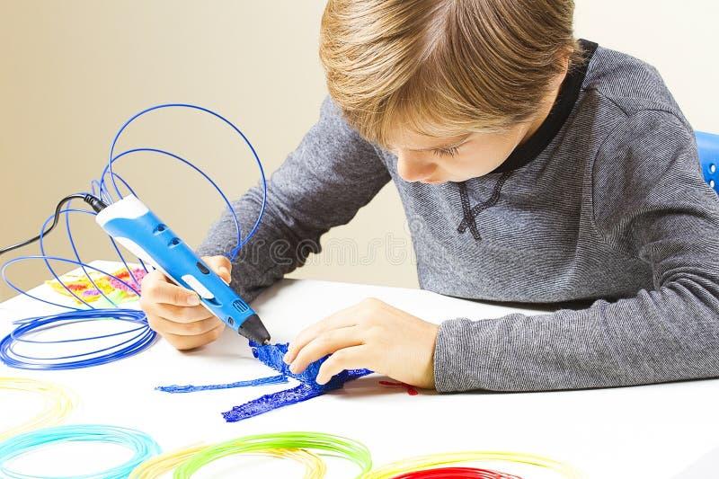 Fokuserat barn med pennan för printing som 3d skapar en nivå royaltyfri fotografi