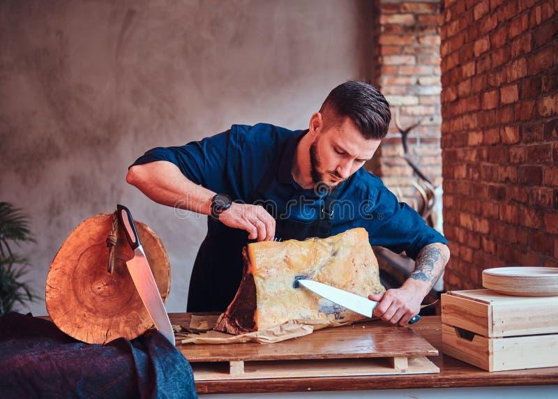 Fokuserat bitande exklusivt knyckigt kött för kockkock på en tabell i kök med vindinre arkivbilder