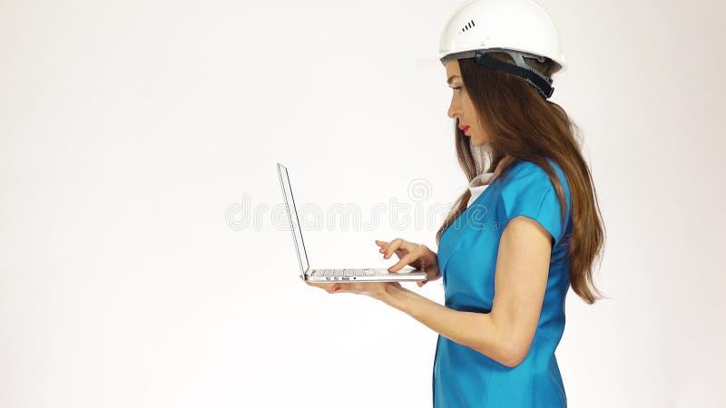 Fokuserat kvinnligt bära för tekniker eller för arkitekt hade hattbruk bärbara datorn mot vit bakgrund arkivbild