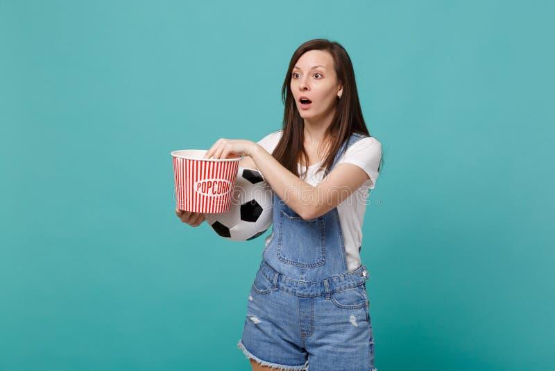 Fokuserat lag för service för match för ung flickafotbollsfan hållande ögonen på favorit- med fotbollbollen, hink av popcorn som  fotografering för bildbyråer