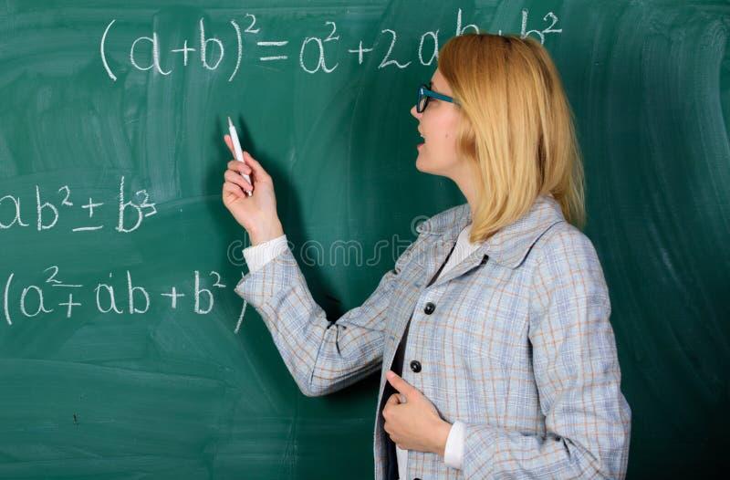 Fokuserat p? examen l?rare p? skolakurs p? svart tavla Kvinna i klassrum skola Hem- skolg?ng lycklig kvinna _ arkivbilder