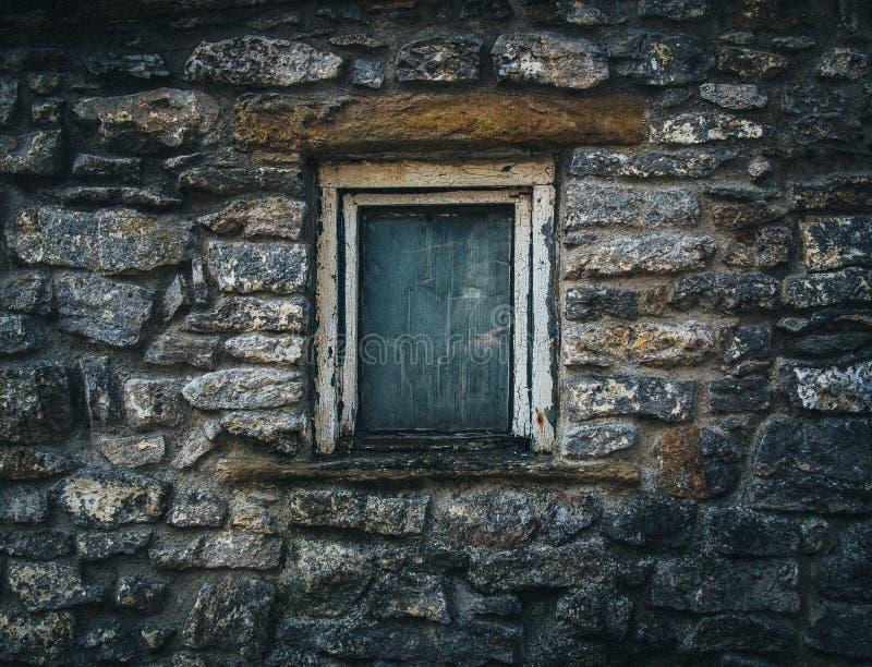 Fokuserat skott av ett litet fönster av en gammal stenstruktur i bygden arkivfoton