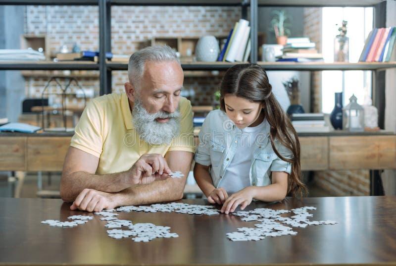 Fokuserat två utvecklingar av familj som spelar pusselleken tillsammans royaltyfri foto