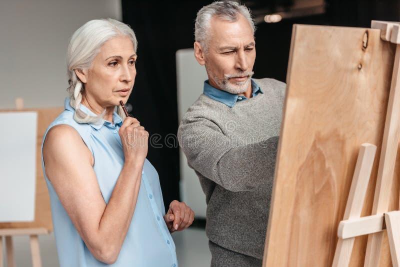 fokussierte ältere Studenten, die zusammen malen lizenzfreie stockfotos