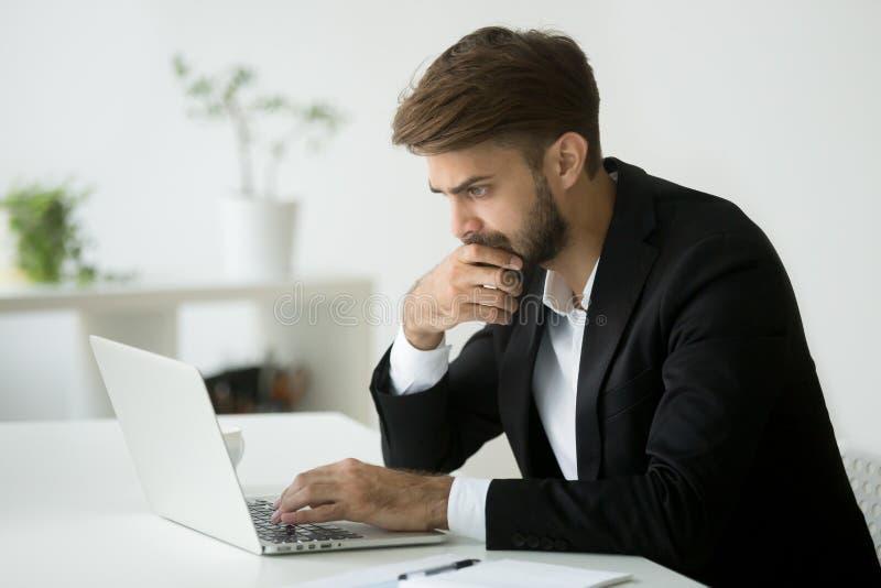 Fokussierte denkende lesende on-line-Nachrichten des ernsten Geschäftsmannes unter Verwendung L stockfoto