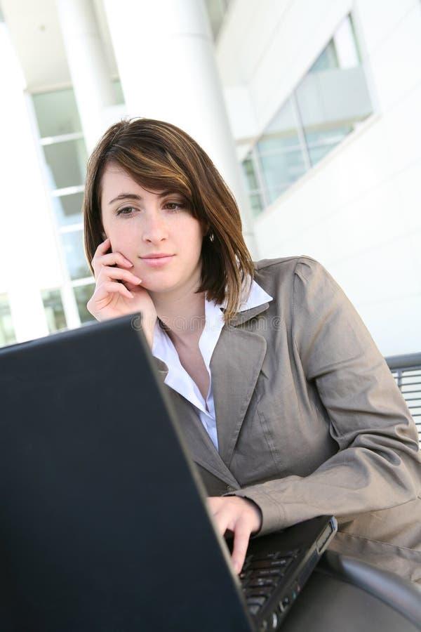 Fokussierte Frau auf Laptop-Computer stockfotografie
