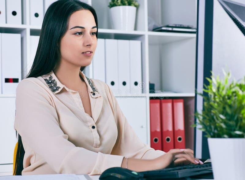 Fokussierte Geschäftsfrau, die am Schreibtisch im kreativen Büro arbeitet lizenzfreie stockfotografie