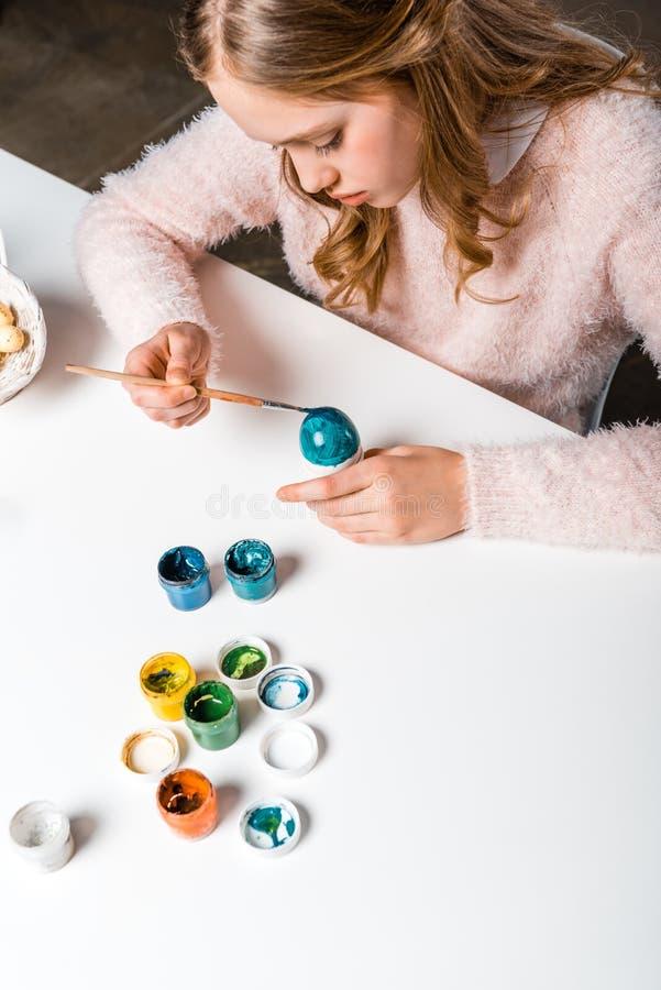 Fokussierte Jugendliche, die bei Tisch Osterei malt stockfoto