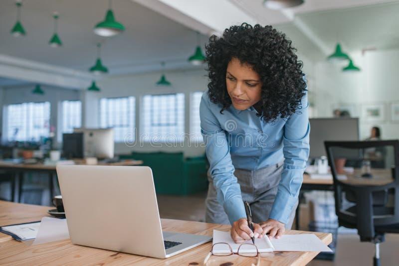Fokussierte junge Geschäftsfraustellung an ihren Schreibtischschreibensanmerkungen stockfoto