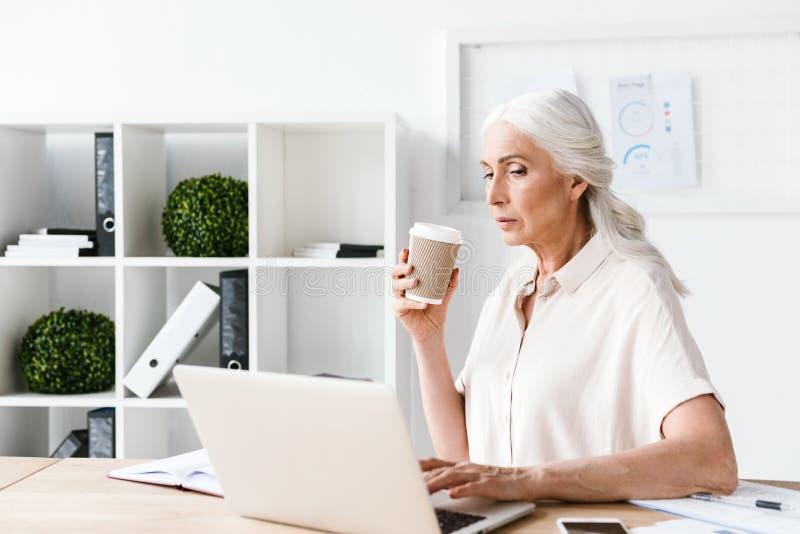 Fokussierte reife Geschäftsfrau, die an Laptop arbeitet lizenzfreie stockfotos