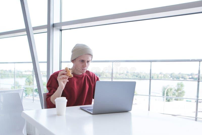 Fokussierte tragende Freizeitbekleidung des jungen Geschäftsmannes arbeitet an einem Laptop in einem Café und isst ein Sandwich stockfoto