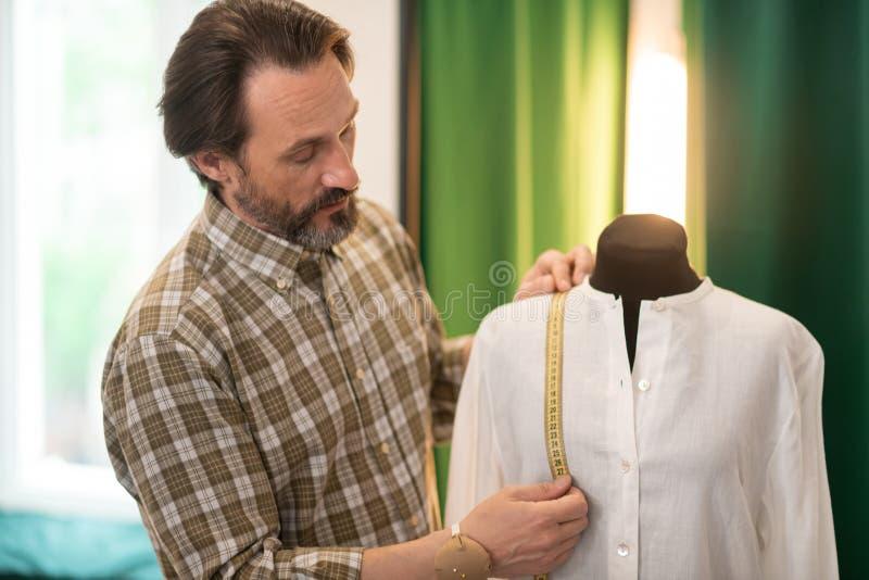 Fokussierter bärtiger Designer, der Maße eines fertigen weißen Hemdes erhält lizenzfreies stockbild