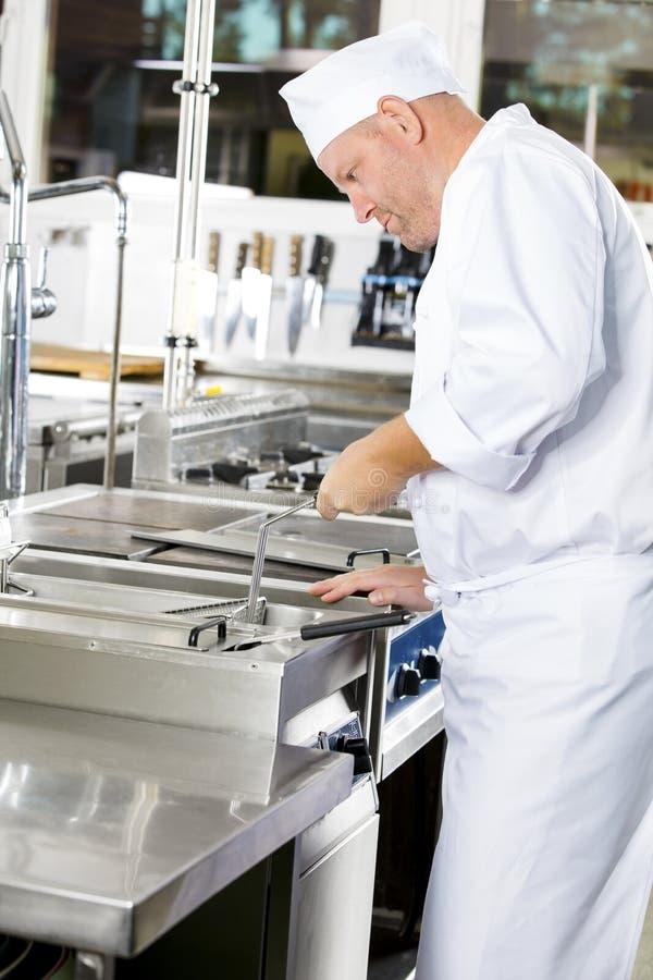 Fokussierter Chef, der Lebensmittel in der Bratpfanne an der großen industriellen Küche brät lizenzfreie stockfotos