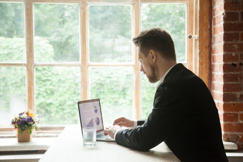 Fokussierter ernster Geschäftsmann, der an dem Laptop analysiert Projekt arbeitet stockfotografie