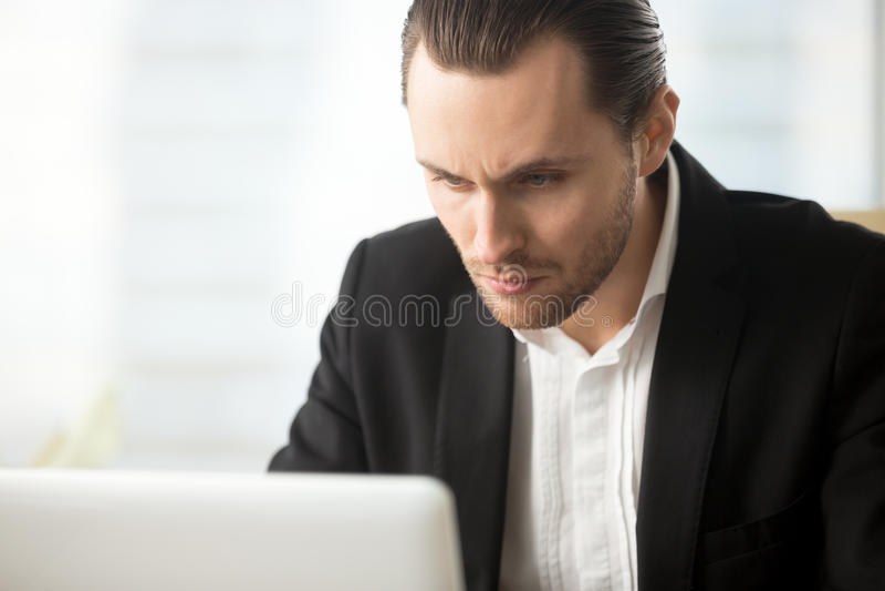 Fokussierter Geschäftsmann, der auf Laptopschirm schaut lizenzfreies stockbild