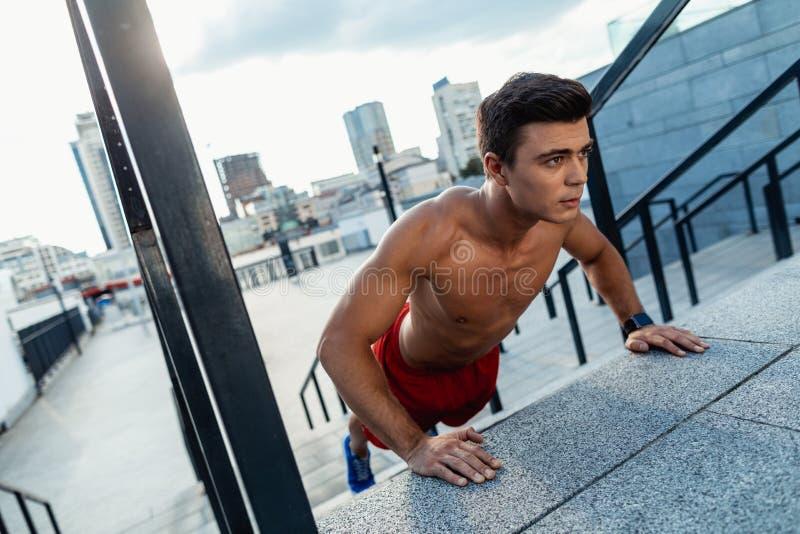 Fokussierter junger Mann, der draußen körperliche Bewegungen macht stockfotografie