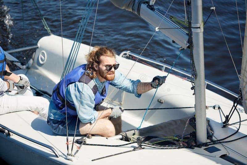 Fokussierter Mann im Segelboot stockfotografie