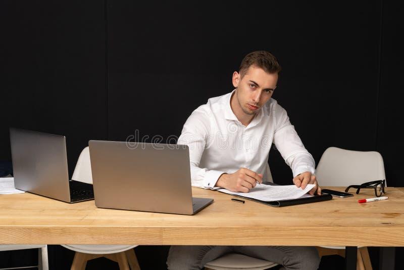 Fokussierter serios Geschäftsmann, der an on-line-Aufgabe denkt stockbild