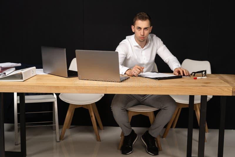 Fokussierter serios Geschäftsmann, der an on-line-Aufgabe denkt lizenzfreie stockbilder