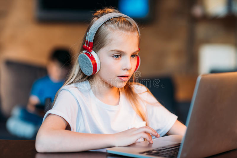 Fokussiertes kleines Mädchen in den Kopfhörern unter Verwendung des Laptops stockfotos