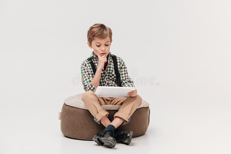 fokussiertes Sitzen des kleinen Jungen und Anwendung der digitalen Tablette lizenzfreie stockbilder