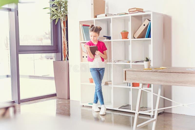 Fokussiertes Stellungs- und Lesebuch des kleinen Mädchens im Büro lizenzfreie stockbilder