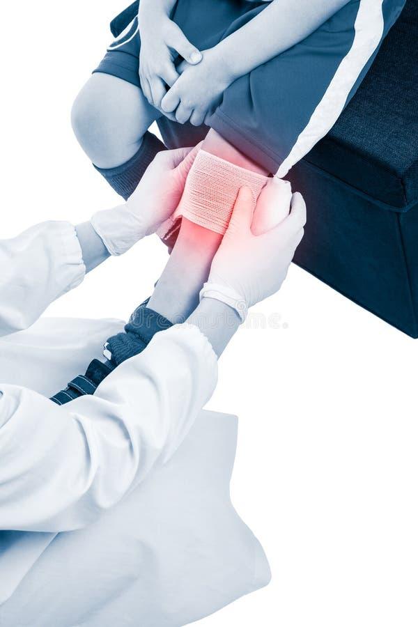 Folâtre des blessures Le docteur fait le bandage sur le patient de genou, sur le Ba blanc photographie stock