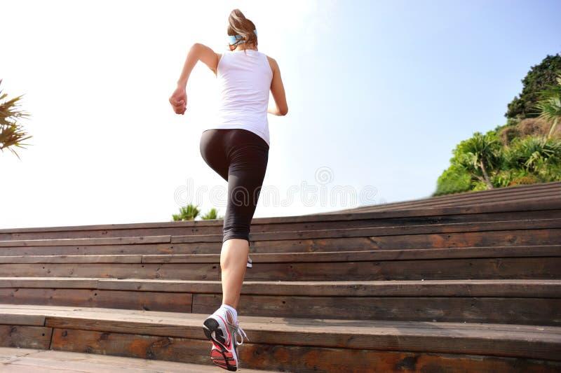 Folâtre la femme courant sur les escaliers en bois photo stock