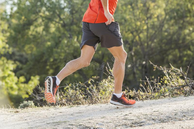 Folâtrez l'homme avec les jambes sportives et musculaires déchirées courant le downhil photographie stock libre de droits