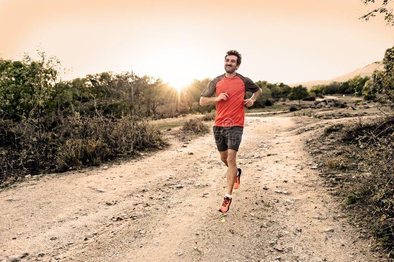Folâtrez l'homme avec les jambes sportives et musculaires déchirées fonctionnant en descendant outre de la route dans la séance d photos libres de droits
