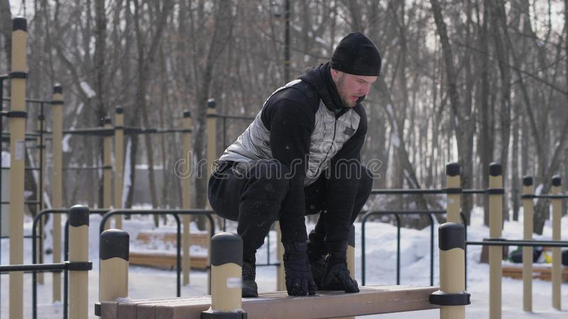 Folâtrez l'homme sautant sur le banc sur la formation de crossfit à l'au sol de sport extérieur photographie stock