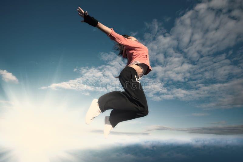 Folâtrez la femme branchant et volez au-dessus du ciel et du soleil photographie stock