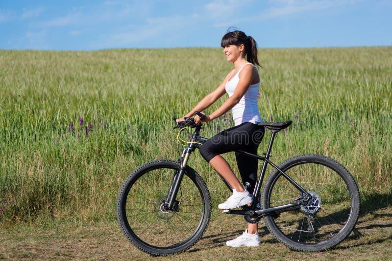 Folâtrez la femme de vélo sur le pré avec un beau paysage photos libres de droits
