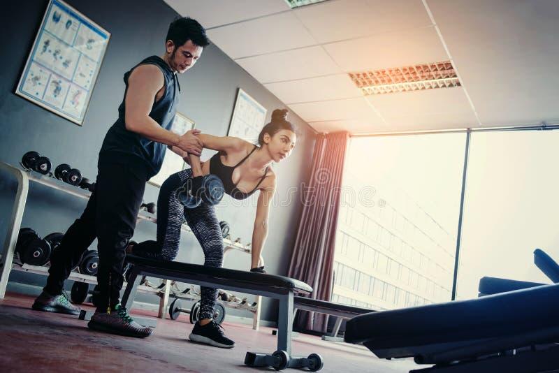 Folâtrez la fille faisant des exercices de poids fonctionnant avec les haltères lourdes h image stock