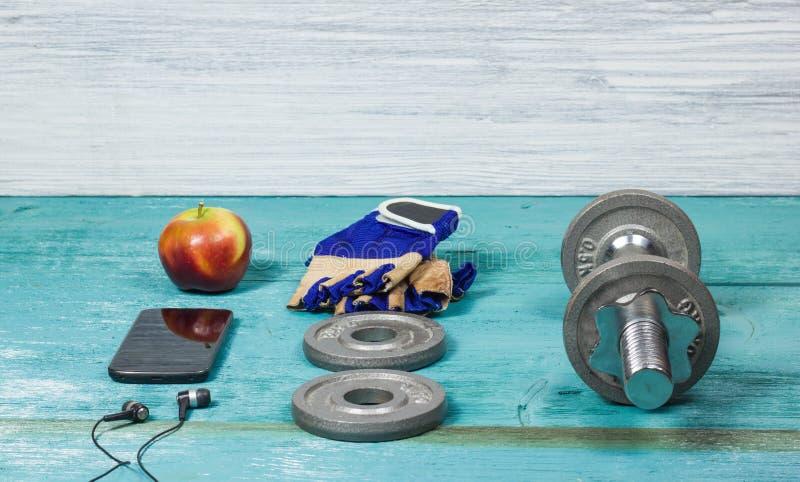 Folâtrez les articles bouteille, les haltères, gants sur le plancher de sport photos libres de droits